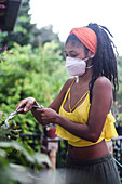 Young woman gardening in face mask