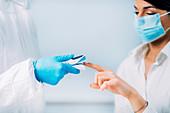 Medical worker checking blood oxygen of coronavirus patient