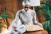 Senior woman preparing DNA test kit