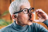 Senior woman inhaling medicine from asthma pump