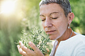Woman enjoying the scent of rosemary