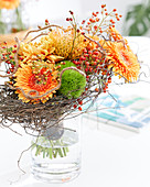 Herbststrauß mit Gerbera, Chrysanthemen, Nadelkissen-Protea, Hagebutten und Moos, Ranken vom Drahtwein als Manschette