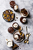 Individual chocolate puddings served with whipped coconut cream and a pretzel bark.