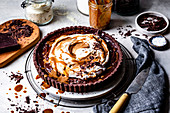 Chocolate caramel tart with whipped coconut cream, caramel and chocolate shavings.