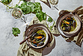 Mediterranean style dinner. Flat-lay of table with Mussels in green sauce and white wine, top view.