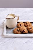 Hafer-Chocolate Chip Cookies mit einem Krug Milch auf Holztablett