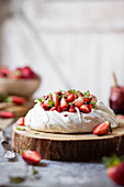 Pavlova cake with strawberries on the table. Front view