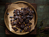 Gold tray of chocolate bark with berries and nuts on a rustic board and distressed, green table.