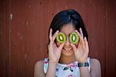 Mädchen hält Kiwis vor die Augen