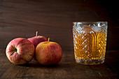 Drei Äpfel und ein Glas mit Apfelsaft auf Holzuntergrund