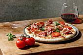 Pizza Napoli mit Schinken und Tomaten serviert mit Rotwein