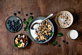 Homemade crunchy puffed millet grain granola with dried fruits and nuts in ceramic bowl, with yogurt, mint and ingredients above. Brown texture background. Flat lay, space. Healthy food breakfast