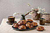 Traditional Swedish cinnamon sweet buns Kanelbulle on vintage tray, cup of coffee, jug of syrup, blossom branches on linen table cloth.