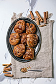 Traditional Swedish cinnamon sweet buns Kanelbulle on vintage tray, cinnamon sticks on linen cloth over white marble background. Flat lay, space.