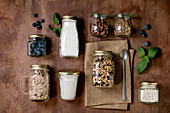 Homemade crunchy puffed millet grain granola with dried fruits and nuts, yogurt, milk, muesli in different glass jars, mint. Brown background. Flat lay, space. Healthy food eco friendly breakfast
