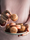 Heap of french macarons on pink plate in hands of woman dressed in pink clothes. Vertical. Copy space