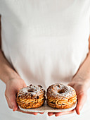 Woman in white t-shirt holds plate with two Choux Paris Brest pastry with hazelnut