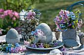 Osterdekoration mit Strauß aus Hyazinthen und Vergißmeinnicht, Zement-Ostereier mit Spitzenband und Blüten, Drahtkorb mit Wachteleiern
