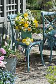 Strauß aus Narzissen und Brautspiere auf Stuhl am Teehaus