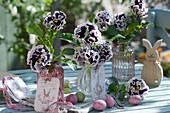 Vasen mit gekräuselten Stiefmütterchen 'Purple White Rim' als Osterdeko mit Ostereiern, Osterhase und Anhängern