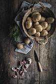 Kartoffeln und Knoblauchzehen auf rustikalem Holztisch