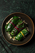 Japanese inspired rainbow chard rolls, filled with mushrooms and finished in a miso broth. They are served on brown rice in a brown stoneware bowl, with chopsticks alongside.