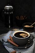 Eine Tasse schwarzer Kaffee serviert mit Schokoladengebäck