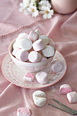 Round pink and white marshmallows in a bowl with two cut in half with scissors.