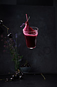 A floating Gin Sour with beetroot and cherries