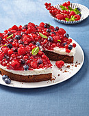 A brownie cake with sour cream and summer berries, sliced