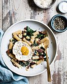 Penne pasta with spinach, bacon and a fried egg on a plate.