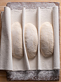 Ungbackene vorgeformte Brote im Couche (Leinentuch)