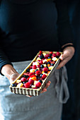 Berry Tart being held by a cook