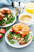 Breakfast sandwich on a croissant with turkey, arugula, strawberries and brie