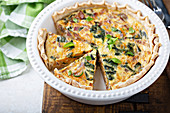 Spinach and bacon quiche cut up in a baking dish