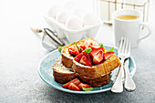 Spiked strawberry french toasts with powdered sugar