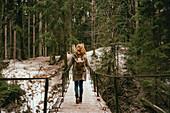 Redhead woman with backpack on footbridge in snowy woods