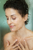 Sensual woman taking a shower behind wet glass