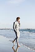 Barefoot businessman talking on smart phone on sunny ocean beach, Los Angeles, California