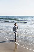 Barefoot businessman talking on smart phone in sunny ocean surf, Los Angeles, California