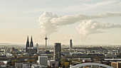 Smoke rising from factories behind Cologne cityscape, Germany
