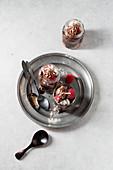 Layered desserts with chocolate cream, pastries, meringue and raspberries
