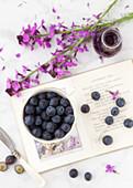 Stillleben mit Blaubeeren, lila Blüten und Buch