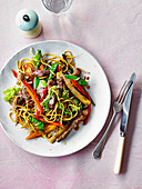 Stir-fried peppered beef steak with noodles and vegetable