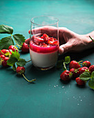 Vegan coconut panna cotta in a glass with strawberry groats