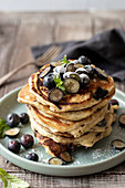 Blueberry pancakes with bluberries, icing sugar and mint