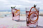 Rosa Gin Tonic mit rosa Pfeffer, Minze, Zimt und Orange im Sonnenlicht auf Restauranttisch