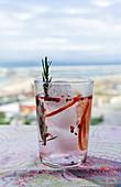 Rosa Gin Tonic mit rosa Pfeffer, Rosmarin und Orange im Sonnenlicht auf Restauranttisch
