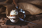 Glass of sweet dessert with chocolate and coffee garnished with cream placed on wooden table near metal scoop with coffee beans