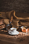 Fresh black coffee in white ceramic cup placed on saucer near coffee grinder and coffee beans on wooden table